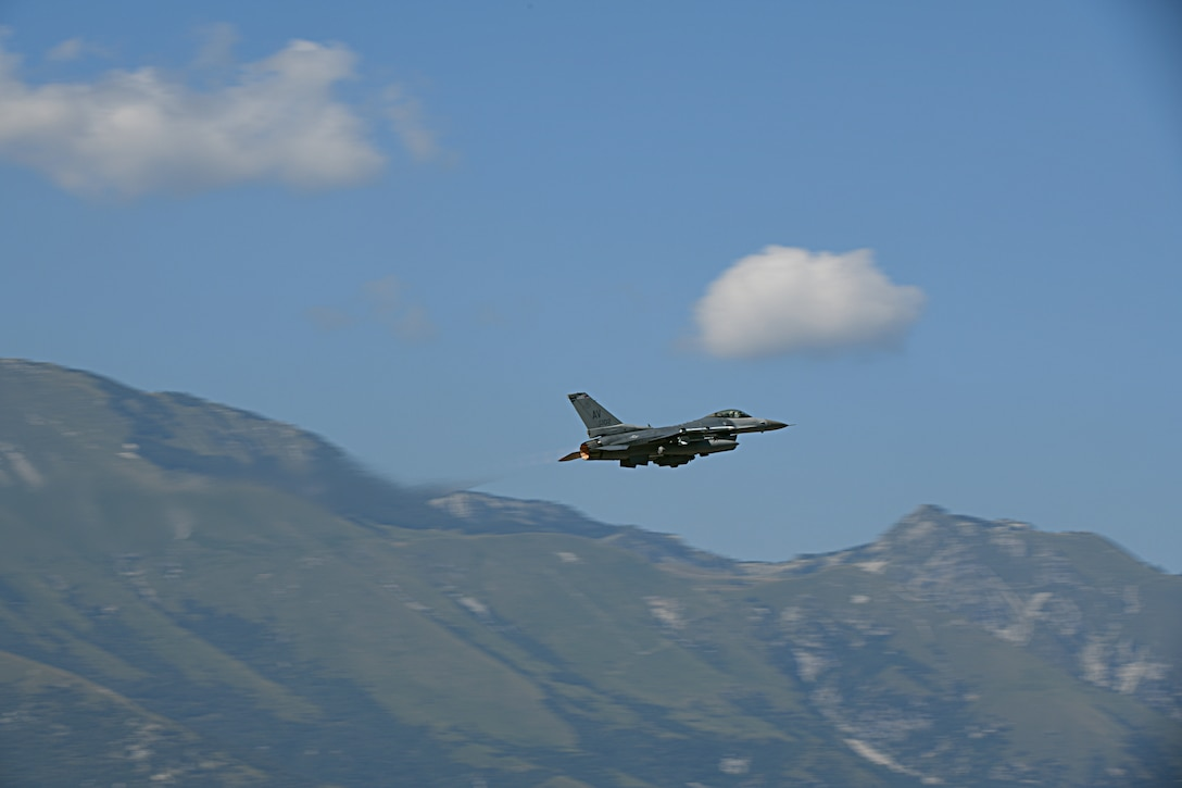 A military jet flies upwards with blue sky and mountains in the background.