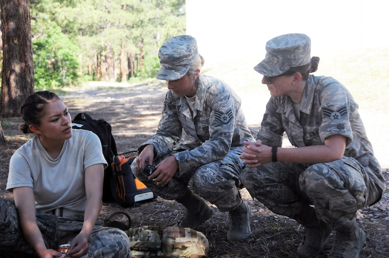 Staff Sgt. Jessica Lang (center) and Senior Airman Erica Wyeth (right), 445th Aerospace Medicine Squadron aerospace medical technicians, evaluate a cadet for a medical emergency during a cadet mock-deployment training event at the Air Force Academy, Colorado Springs, July 23, 2019.