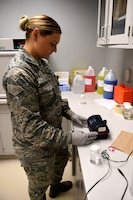 A woman in ABUs tests a water sample.