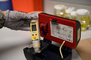 A hand holds a device for measuring the chlorine in water.