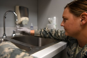 A woman wearing ABUs gets water from a faucet.