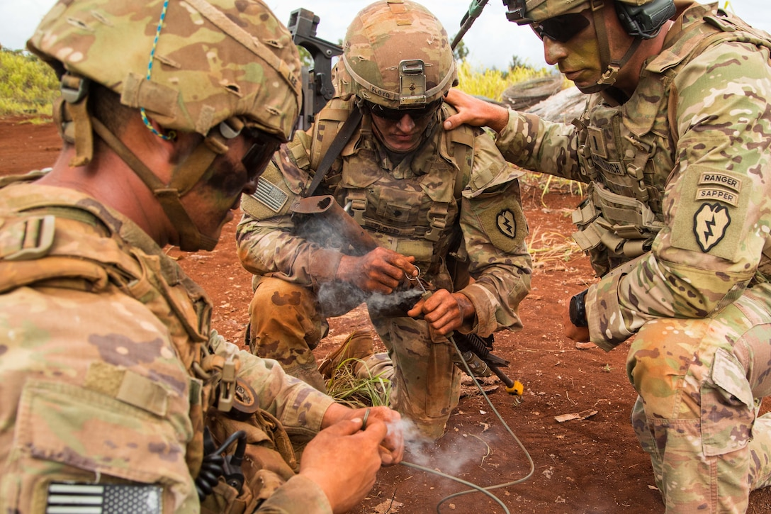 Three soldiers kneel in a circle as one of them lights a detonation wire.