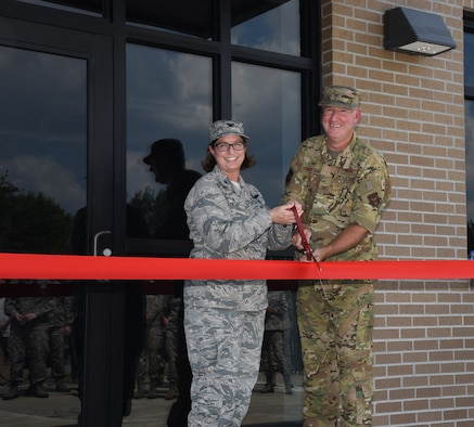 Col. Deborah A. Deja, 36th Aeromedical Evacuation Squadron commander, and Col. Jeffrey Van Dootingh, 403rd Wing commander, pose for a photo before cutting the ribbon in front of 36th AES's new building at Keesler Air Force Base, Miss., September 7, 2019. The 36th AES is responsible for the in-flight care of wounded service-members as they are transported to a medical facility equipped for critical situations (U.S. Air Force photo by Senior Airman Kristen L. Pittman).