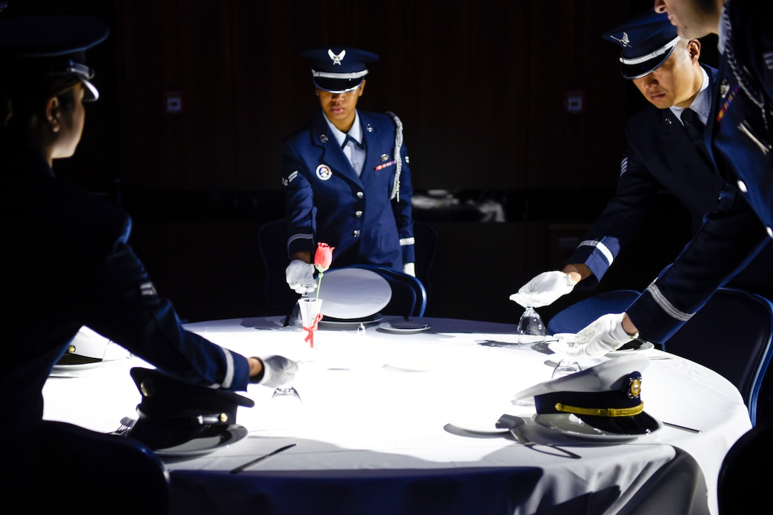 Airmen stand around a table.