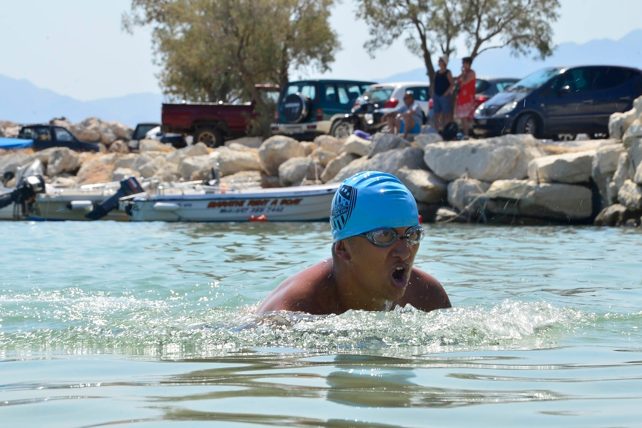 A man wearing goggles and a blue bathing cap swims.
