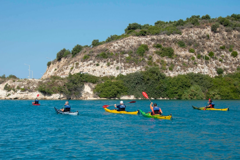 Kayakers paddle on blue water with green mountains in the background.