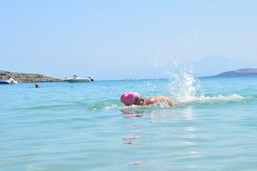A woman wearing goggles and a pink bathing cap swims.