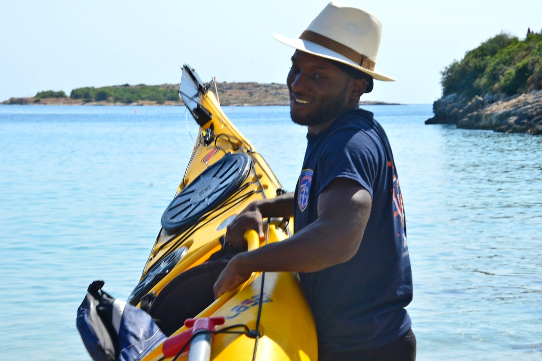 Man carries yellow kayak.