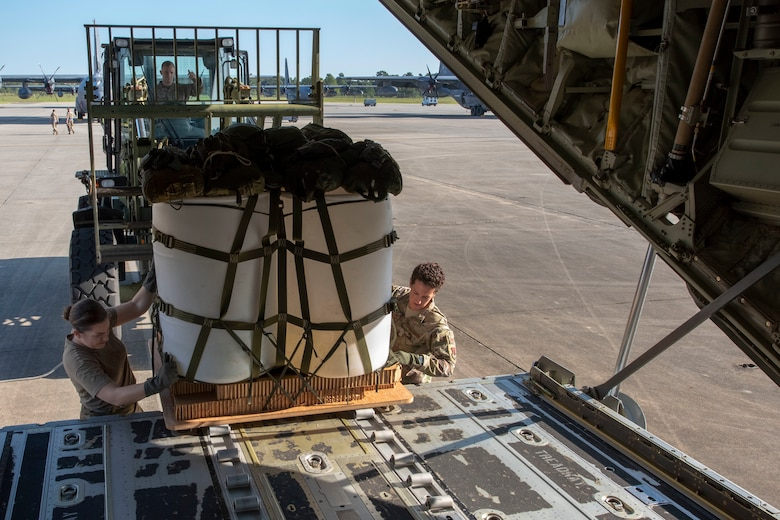 Senior Airman Rachel Bissonnette, left, and Tech. Sgt. Colleen McGahuey-Ramsey, right, both 71st Rescue Squadron (RQS) loadmasters, move a container delivery system on to the ramp of a HC-130J Combat King II before the airframe's first flight to be operated by an all-female aircrew Sept. 6, 2019, at Moody Air Force Base, Ga. The 71st RQS provides rapidly deployable, expeditionary personnel recovery forces for contingency and crisis response operations worldwide. (U.S. Air Force photo by 2nd Lt. Kaylin P. Hankerson)