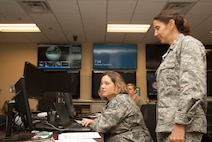 U.S. Air Force Maj. Ileana O'Shea, 165th Logistics Readiness Squadron director of operations, receives an update on current weather conditions from Master Sgt. Kristina Pratt, 165th AW installation emergency manager Sept. 4, 2019. Mission essential personnel are sustaining 24-hour operations to protect military assets and ensure personnel are evacuated ahead of Hurricane Dorian. In the storm's aftermath, Airmen of the 165th Airlift Wing are prepared to assist local and state authorities, and their residents, as they are affected by Hurricane Dorian.