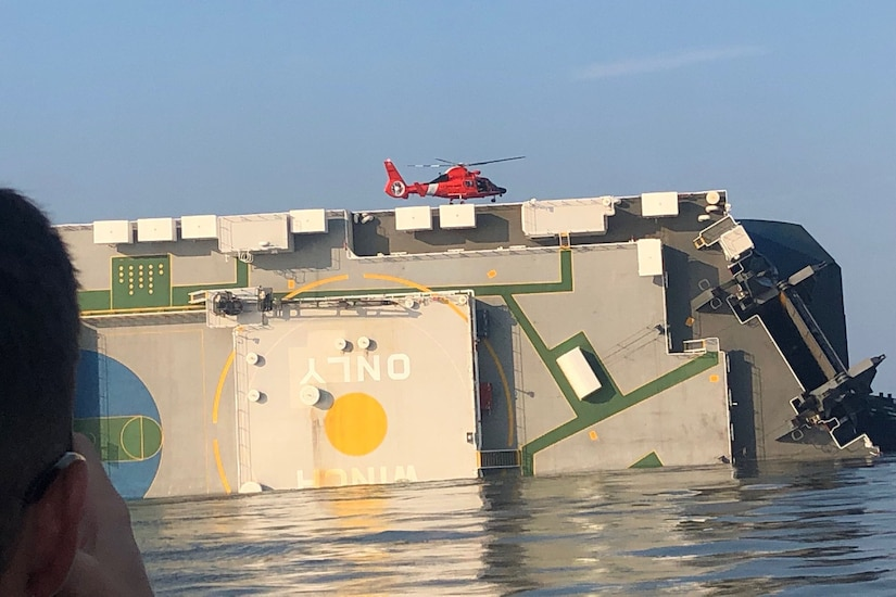 A helicopter flies above a ship on its side.