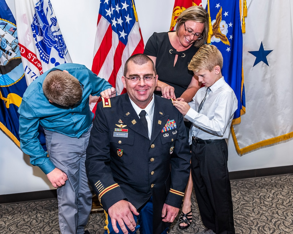 Family replaces rank patches on Army officer's uniform with new rank.