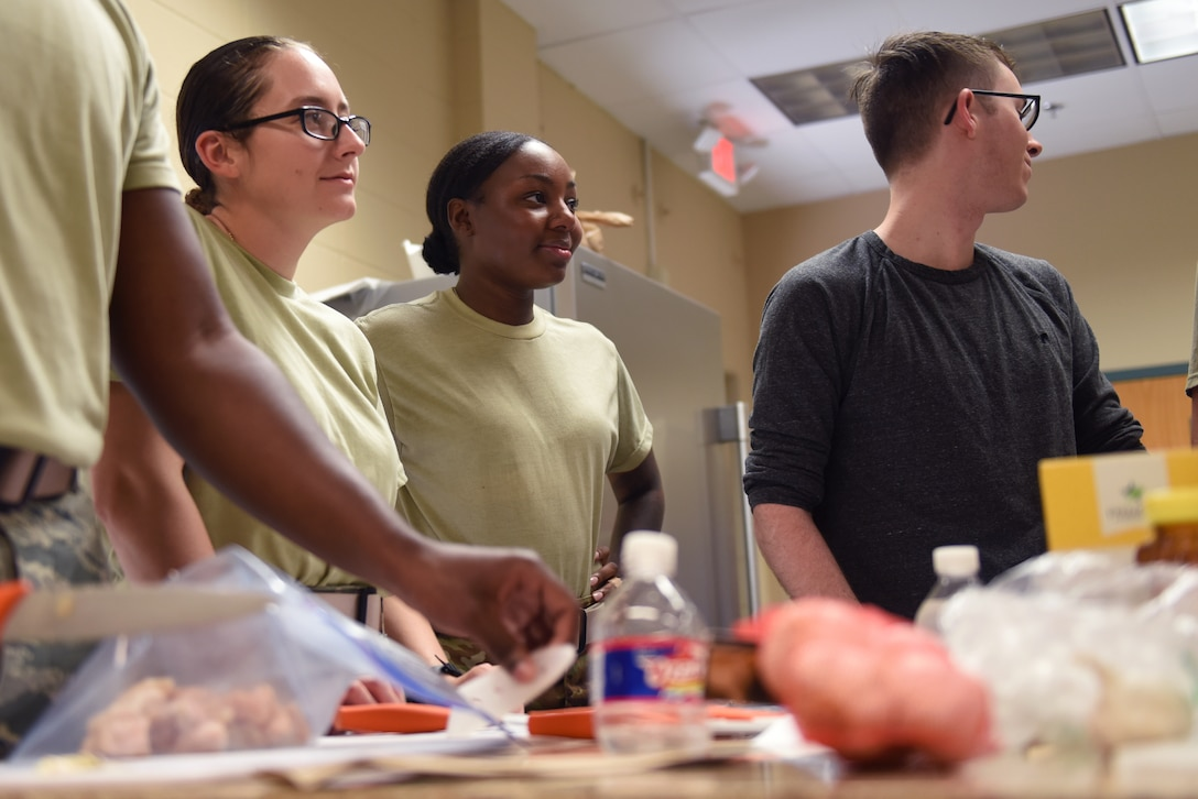 Keesler Air Force Base Airmen learn cooking techniques at the Dorm to Gourmet cooking class inside the McBride Commons on Keesler Air Force Base, Sept. 5, 2019. The cooking class was held to not only improve the cooking skills of Airmen but to build team connection and resiliency. (U.S. Air Force photo by Airman Seth Haddix)