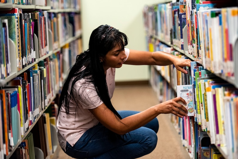 Yoselin Kilpatrick, 23d Force Support Squadron library aid, returns a book Sept. 5, 2019, at Moody Air Force Base, Ga. With more than 10k books available at the library, it's just one of the many benefits at the Information Learning Center available to Airmen and families. (U.S. Air Force photo by Senior Airman Erick Requadt)