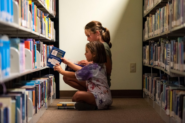 Zophia, front, and Athena, daughters of Lindsay Clark, military spouse, pick out a book Sept. 5, 2019, at Moody Air Force Base, Ga. The Information Learning Center provides a means of morale and serves as the central hub for all informational and educational growth for Airmen and families. (U.S. Air Force photo by Senior Airman Erick Requadt)