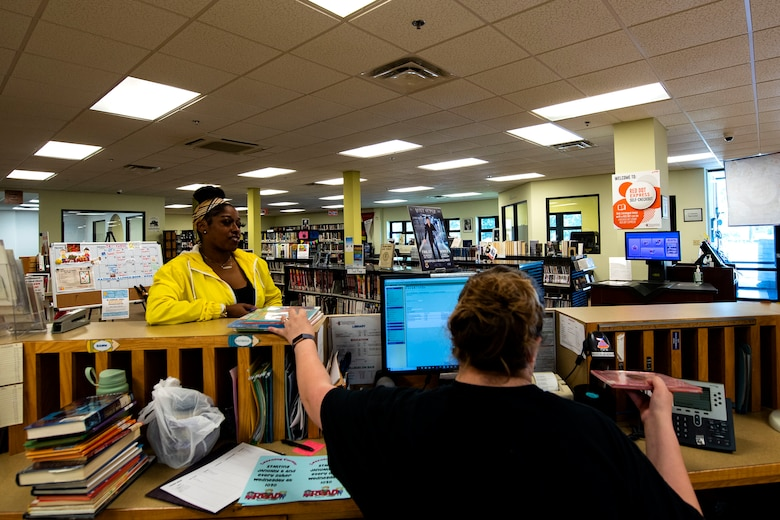 Katrina True, right, 23d Force Support Squadron library aid, checks books out to Candice Wilson, 23d Medical Group appointment clerk and military spouse, Sept. 6, 2019, at Moody Air Force Base, Ga. The Information Learning Center provides a means of morale and serves as the central hub for all informational and educational growth for Airmen and families. (U.S. Air Force photo by Senior Airman Erick Requadt)