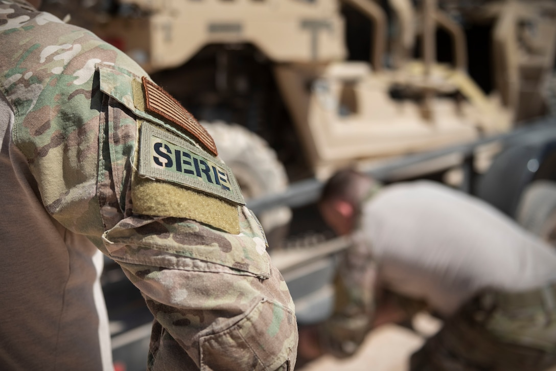 A survival, evasion, resistance, and escape (SERE) specialist assigned to the 414th Combat training Squadron, watches as another SERE specialist straps down heavy equipment on the Nevada Test and Training Range (NTTR), August 29, 2019