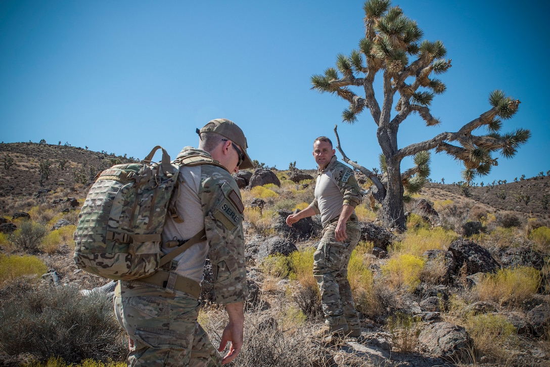 Tech. Sgt. Gary Roland and Tech. Sgt Jack Maher, survival, evasion, resistance, and escape (SERE) specialists assigned to 414th Combat Training Squadron (CTS), navigate a hill on the Nevada Test and Training Range, August 29, 2019.