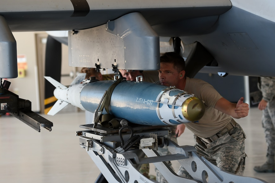 A 432nd Maintenance Group Airman loads a bomb onto an MQ-9 Reaper at Creech Air Force Base, Nevada, July 19, 2019. Load competitions are held to showcase and highlight maintenance group weapons Airmen. (U.S. Air Force photo by Airman 1st Class William Rio Rosado)