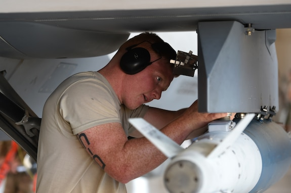 A 432nd Maintenance Group Airman secures a bomb on an MQ-9 Reaper at Creech Air Force Base, Nevada, July 19, 2019. The crews don't know about which bombs or missiles they'll be loading until the day of the competition. (U.S. Air Force photo by Airman 1st Class William Rio Rosado)
