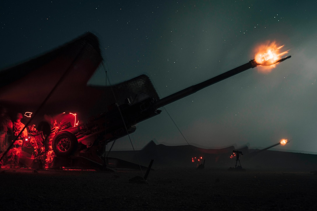 Marines fire a howitzer at night.
