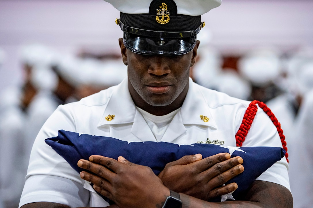 A sailor holds a folded American flag to his chest.