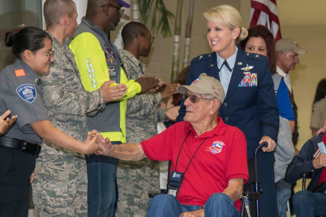 A veteran being pushed in a wheelchair by an airman shakes hands with a civilian.