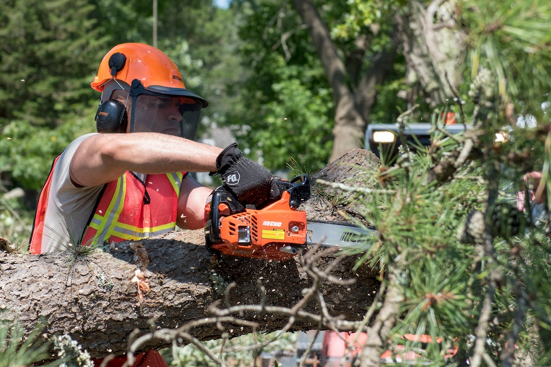 An airman uses a chainsaw on a fallen tree.