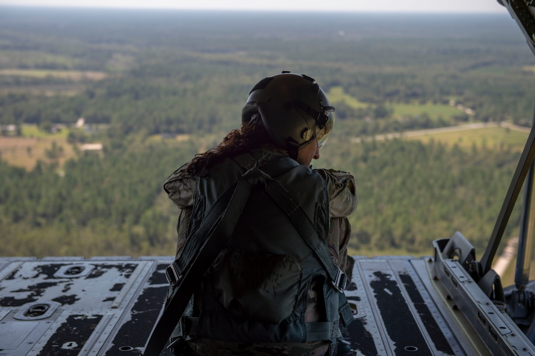 Tech. Sgt. Colleen McGahuey-Ramsey, 71st Rescue Squadron (RQS) loadmaster, looks out the back of an HC-130J Combat King II as it flies over south Georgia Sept. 6, 2019, at Moody Air Force Base, Ga. This was the first flight for the 71st RQS and the HC-130J Combat King II airframe to be operated by an all female aircrew. The 71st RQS provides rapidly deployable, expeditionary personnel recovery forces for theater commanders for contingency and crisis response operations worldwide. (U.S. Air Force photo by 2nd Lt. Kaylin P. Hankerson)