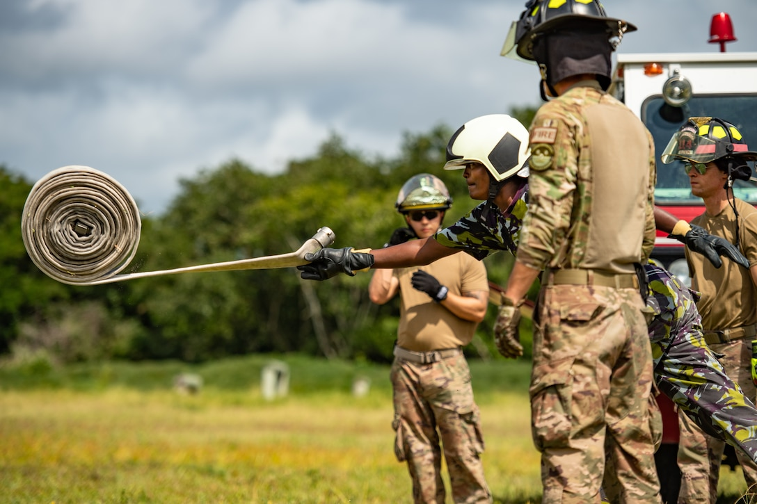 A Kenya Navy firefighter unravels a firehose during a training circuit at Manda Bay, Kenya, Aug. 29, 2019. The training, held by 475th Expeditionary Air Base Squadron firefighters, was designed to build upon the established partnership between the two nations by enforcing teamwork and endurance while enhancing technical proficiency. (U.S. Air Force photo by Staff Sgt. Devin Boyer)