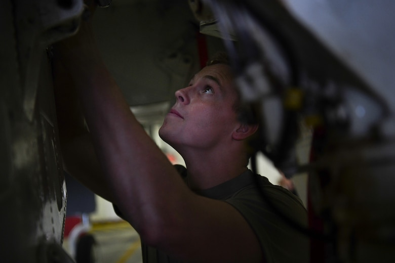 A crew chief assigned to the 48th Equipment Maintenance Squadron conducts an F-15 phase inspection at Royal Air Force Lakenheath, England, Aug. 13, 2019. Phase inspections that take place every 400 flight hour and focus on structural and systems integrity of the aircraft. (U.S. Air Force photo by Airman 1st Class Shanice Williams-Jones)