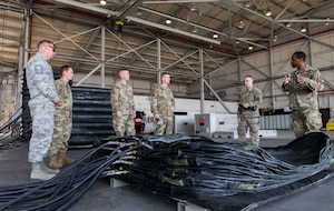 U.S. Air Force Tech. Sgt. Mitchell Brewington (far right), 39th Maintenance Squadron transient alert crash and recovery section chief, explains the capabilities of pneumatic lifting bags to leadership from the 39th Air Base Wing during a 39th MXS immersion tour Sept. 5, 2019, at Incirlik Air Base, Turkey. The lifting bags assist the section with performing their primary mission of ensuring the runway is clear and ready to support NATO's southern region. (U.S. Air Force photo by Staff Sgt. Ceaira Tinsley)