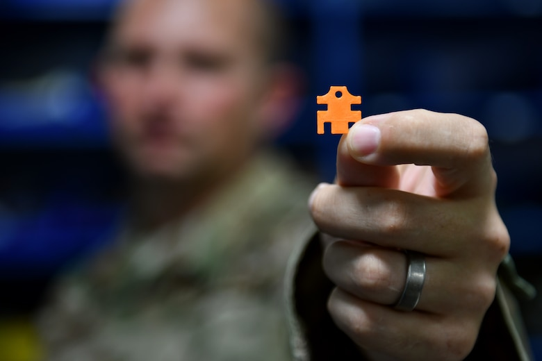 U.S. Air Force Tech. Sgt. Keith Boudreau, 31st Maintenance Group Air Force Repair Enhancement Program technician, holds a 3D printed spacer he created, Sep. 5, 2019, at Aviano Air Base, Italy. Spacers made by the AFREP technicians repaired 474 phones, saving the 31st Fighter Wing $106,176. (U.S. Air Force photo by Senior Airman Kevin Sommer Giron)