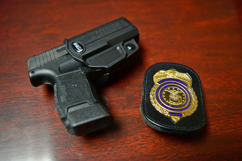 A photo of a pistol and an OSI badge on a table.