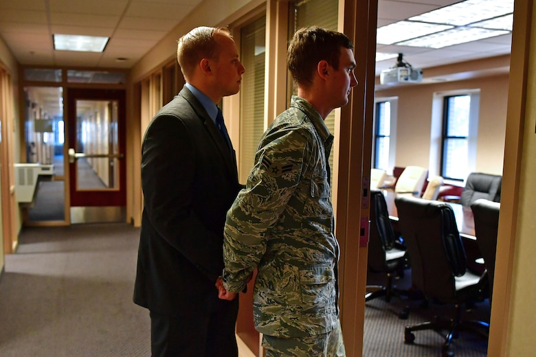 An Airman is walked into an interview room while in handcuffs.