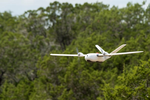 An unmanned aerial system flies over Camp Bullis, Texas, during a field test Sept. 4. The UAS was equipped with Light Detection and Ranging, multi-spectral sensors and machine-learning algorithms to map, survey and inventory habitat for the golden-cheeked warbler. The field test will help the Air Force determine if UAS technology can characterize habitat better, faster and cheaper than current methods.