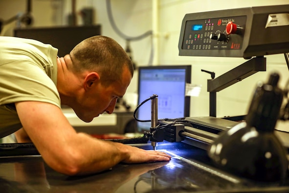 Tech. Sgt. Tyler Williams, 445th Maintenance Squadron, aircraft metals technician, operates an engraving machine at the fabrications and metal technologies shop Aug. 4, 2019.