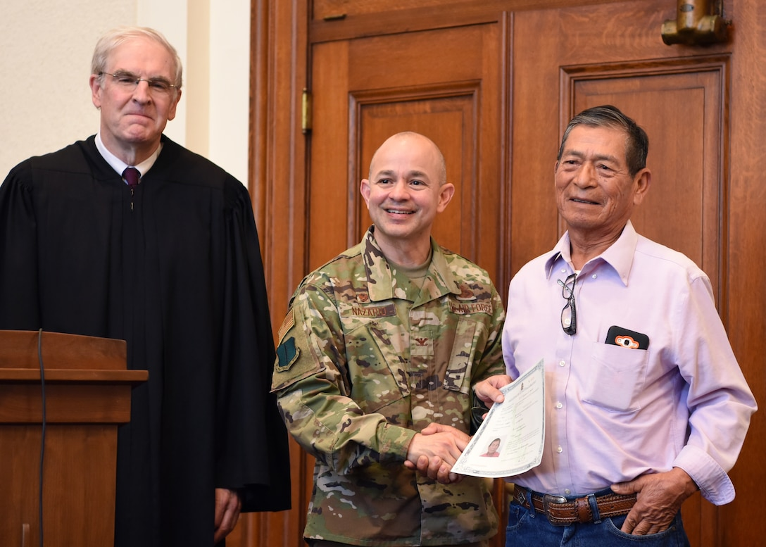 U.S. Air Force Col. Andres Nazario 17th Training Wing commander presents a certificate to Antonio Rojo Gonzalez, a new U.S. citizen at the Naturalization Ceremony in the O.C. Fisher Federal Building September 4, 2019. Rojo Gonzalez was the oldest member of the group at 77 years old. (U.S. Air Force photo by Airman 1st Class Ethan Sherwood)
