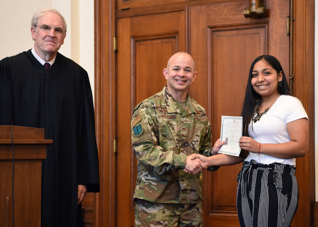 U.S. Air Force Col. Andres Nazario, 17th Training Wing commander presents a certificate to Ruth Sandate Garcia, a new U.S. citizen at the Naturalization Ceremony in the O.C. Fisher Federal Building September 4, 2019. Sandate Garcia was the youngest member of the group at 20 years old. (U.S. Air Force photo by Airman 1st Class Ethan Sherwood)