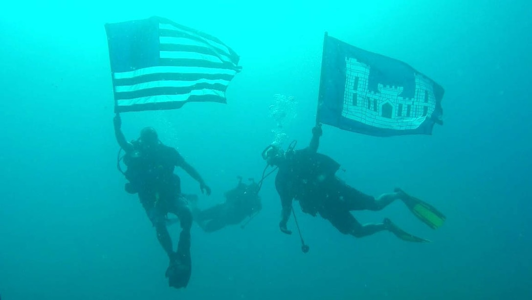 Rick Benoit (left) and Steve England (right) displayed the American and USACE colors after conducting above and below water inspections of waterfront infrastructure from Aug. 13-26 at the U.S. Army Garrison Kwajalein Atoll in the Republic of the Marshall Islands. Benoit and England serve on the the USACE Forward Response Technical Dive Team, which performs underwater inspections around the world on behalf of the Army's Installation Management Command.