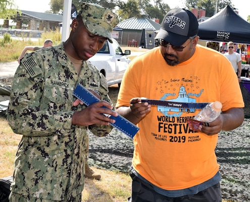 Petty Officer 2nd Class Mark Hambrick, assigned to Navy Recruiting District San Antonio, discusses the various rates of the Navy with an attendee of Mission Pachanga during the annual World Heritage Festival held at Mission Park Pavilion Sept. 7.