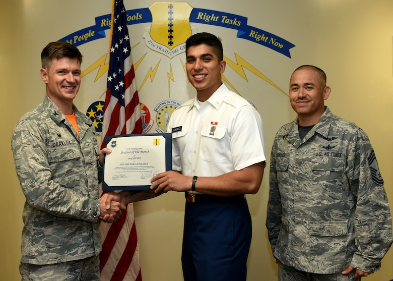 U.S. Air Force Col. Thomas Coakley, 17th Training Group commander, presents the 316th Training Squadron Student of the Month award to U.S. Army Pfc. Hector Gonzalez, 316th TRS student, at Brandenburg Hall on Goodfellow Air Force Base, Texas, September 6, 2019. The 316th TRS's mission is to conduct U.S. Air Force, U.S. Army, U.S. Marine Corps, U.S. Navy and U.S. Coast Guard cryptologic, human intelligence and military training. (U.S. Air Force photo by Airman 1st Class Robyn Hunsinger/Released)