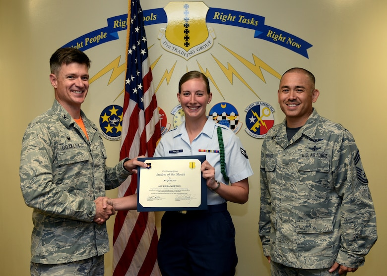 U.S. Air Force Col. Thomas Coakley, 17th Training Group commander, presents the 315th Training Squadron Student of the Month award to Airman 1st Class Kara Norton, 315th TRS student, at Brandenburg Hall on Goodfellow Air Force Base, Texas, September 6, 2019. The 315th TRS's vision is to develop combat-ready intelligence, surveillance and reconnaissance professionals and promote an innovative squadron culture and identity unmatched across the U.S. Air Force. (U.S. Air Force photo by Airman 1st Class Robyn Hunsinger/Released)