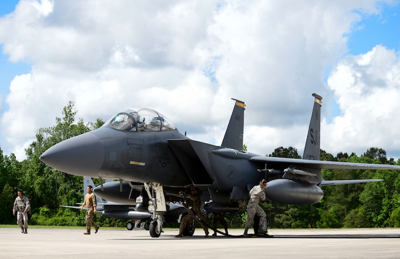 Airmen from multiple Air Force specialty codes perform a hot-pit refuel on an F-15 E Strike Eagle during the Combat Support Wing capstone, May 9, 2019, at Kinston Regional Jetport, North Carolina. A hot-pit is a term used to describe a jet being refueled on the ground while the engines are running. (U.S. Air Force photo by Senior Airman Kenneth Boyton)