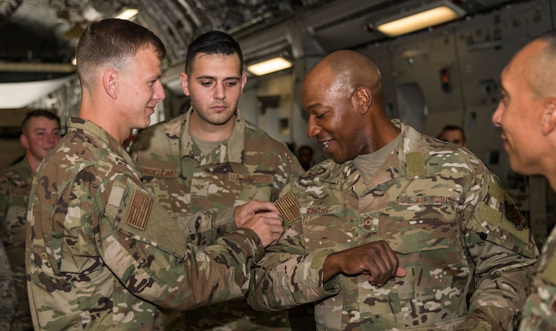 Senior Airman Dean Lemley, 736th Aircraft Maintenance Squadron C-17 dedicated crew chief, places a squadron patch on the sleeve of Chief Master Sgt. of the Air Force Kaleth O. Wright Sept. 4, 2019, at Dover Air Force Base, Del. Wright visited maintenance personnel and aircrew members on the Globemaster III. (U.S. Air Force photo by Roland Balik)