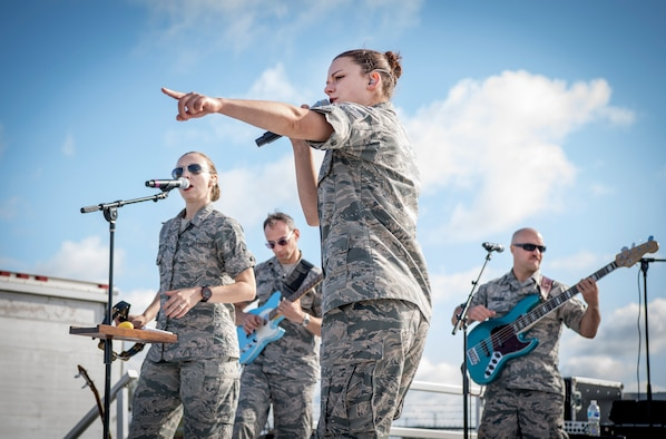 The Band of Mid-America Roots In Blue from Scott Air Force Base, Illinois, performs during Grissom's Air & Space Expo at Grissom Air Reserve Base, Indiana, Sept. 7, 2019. In the photo A1C Dana Bowers, vocalist, is seen using her outgoing personality to entertain waiting lines with help from fellow band members Senior Airman Melissa Edgmon, vocalist/guitarist, Senior Airman Alberto Cosano, guitarist/director, and Airman 1st Class Dusty Carlson, bass guitarist. (U.S. Air Force photo/Master Sgt. Benjamin Mota)