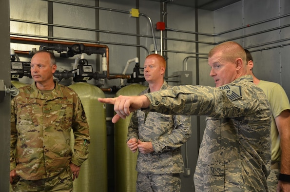 Master Sgt. Michael Scheetz (right), a heating, ventilation and air conditioning project programmer at the Air Force Technical Applications Center, shows AFTAC commander Col. Chad Hartman how he and the recovery response team brought the nuclear treaty monitoring center's HVAC system back online Sept. 5, 2019, after the organization shut down ahead of Hurricane Dorian at Patrick AFB, Fla.  Also pictured is Master Sgt. Chris Gaskill, AFTAC's power production project programmer.  (U.S. Air Force photo by Susan A. Romano)