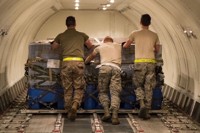"Members of 436th Aerial Port Squadron ramp services section push a pallet into its position in the main cargo deck of an Air Transport International Boeing 757-200 aircraft Sept. 8, 2019, at Dover Air Force Base, Del. The ATI aircraft, part of the Civil Reserve Air Fleet program, was contracted to transport cargo and 30 Team Dover members to Fairchild AFB, Wash., participating in Mobility Guardian 2019. ""We welcome the inclusion of one of our CRAF partners in MG19 as it marks the first time Air Mobility Command has exercised a commercial airlift component of our wartime plan,"" said Maj. Adam Crane, AMC Headquarters CRAF Branch Chief, Scott AFB, Ill. (U.S. Air Force photo by Roland Balik)"