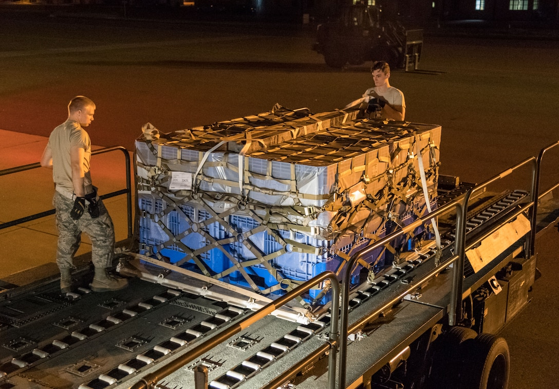"""Members of 436th Aerial Port Squadron ramp services section look over cargo netting prior to loading the last pallet onto an Air Transport International Boeing 757-200 aircraft Sept. 8, 2019, at Dover Air Force Base, Del. The ATI aircraft, part of the Civil Reserve Air Fleet program, was contracted to transport cargo and 30 Team Dover members to Fairchild AFB, Wash., participating in Mobility Guardian 2019. """"Air Mobility Command's commercial airlift partners are a vital part of our daily airlift missions around the world as well as our wartime effort,"""" said Maj. Adam Crane, AMC Headquarters CRAF Branch Chief, Scott AFB, Ill. (U.S. Air Force photo by Roland Balik)"""