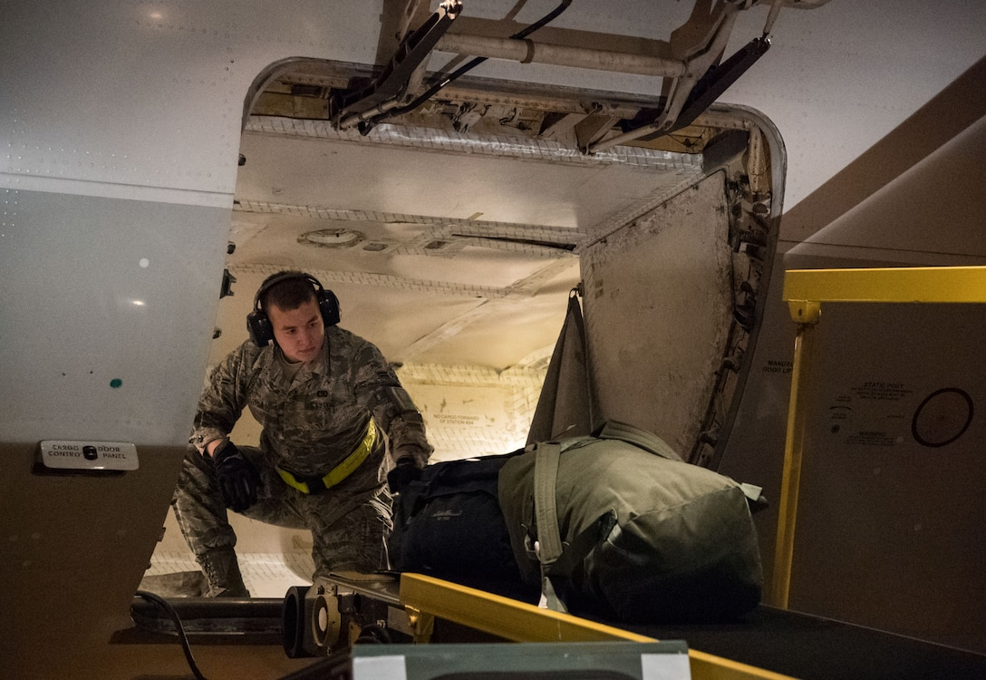 """Airman 1st Class Justin Lepla, 436th Aerial Port Squadron passenger services specialist, loads baggage into the lower cargo hold of an Air Transport International Boeing 757-200 Sept. 8, 2019, at Dover Air Force Base, Del. The ATI aircraft, part of the Civil Reserve Air Fleet program, was contracted to transport cargo pallets and 30 Team Dover members to Fairchild AFB, Wash., participating in Mobility Guardian 2019. """"In support of exercise Mobility Guardian 2019, Air Mobility Command contracted commercial aircraft to simulate activating CRAF marking the first time, in a long time, AMC has exercised a commercial component of its wartime plan,"""" said Maj. Adam Crane, AMC Headquarters CRAF Branch Chief, Scott AFB, Ill. (U.S. Air Force photo by Roland Balik)"""
